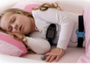 Photo of a child asleep in bed wearing a device around their chest that records physiological parameters